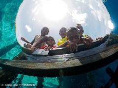 Papuakinder am Steg von Arborek sehen den Taucher